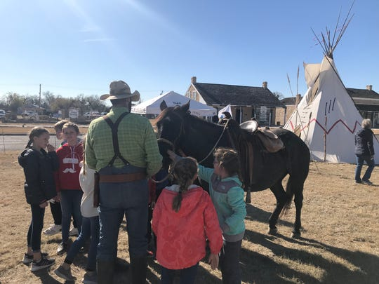 A friendly horse enjoys some attention from San Angelo elementary students as Christmas at Old Fort Concho prepares to commence on Friday, Dec. 6.