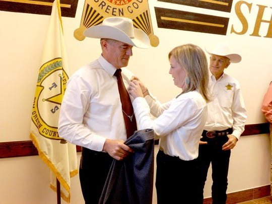 "Kelly Hanna pins a new badge on her husband, recently-retired Texas Ranger John ""Nick"" Hanna, who was sworn in as the new Chief Deputy by Tom Green County Sheriff David Jones, right, on Monday."