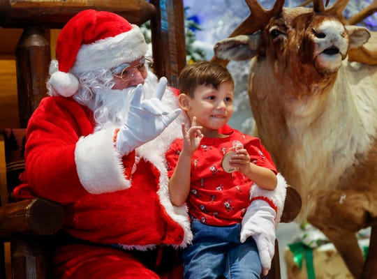 """Skyler Perez, 5, and Santa Claus say """"love"""" in sign language as they have their picture taken at Bass Pro Shops on Friday, Dec. 6, 2019. Santa was using sign language to communicate with deaf and hard-of-hearing children."""