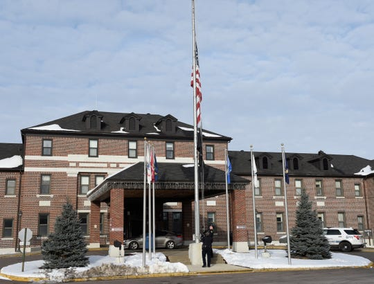 Sgt. Ed Weaver and Officer Nick Busch from the VA police lower a flag to half-staff at 2:05 p.m. on Friday to reflect the moment the Minnesota National Guard lost contact with the UH-60 Black Hawk that crashed on Thursday afternoon Friday, Dec. 6, 2019, at the St. Cloud VA Health Care System.