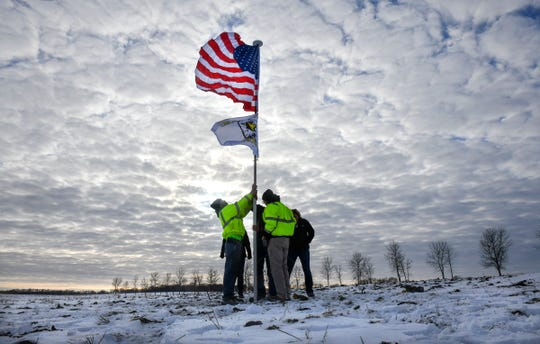 Members of the Krippner family raise  flags Friday, Dec. 6, 2019, in tribute to victims of Thursday's National Guard helicopter crash that happened Thursday on their land near Marty.