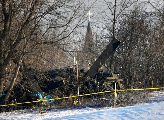 In this Thursday, Dec. 5, 2019, photo the steeple of Holy Cross Catholic Church in Kimball, Minn., rises in the distance over the deadly crash site of a Minnesota National Guard Blackhawk helicopter. (Brian Peterson/Star Tribune via AP)