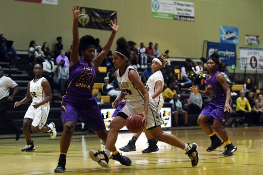 Treasure Coast High School's Denvia Morgan makes a move to the basket around the defense of Fort Pierce Central's Larissa Jennings on Thursday, Dec. 5, 2019, during a District 9-7A game in Port St. Lucie. Treasure Coast won the game 71-24.