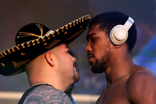 "Heavyweight boxers Anthony Joshua of Britain, right, and Mexican-American Andy Ruiz Jr. face off during a weigh-in at Faisaliah Center in Riyadh, Saudi Arabia, on Friday, Dec. 6, 2019. The first heavyweight title fight in the Middle East, has been called the ""Clash on the Dunes."" It will take place at the Diriyah Arena on Saturday."