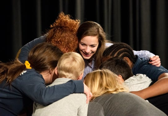Rachel Johnson, middle, huddles with children in the Spartanburg Youth Theatre while doing warm-up exercises during a recent rehearsal for the class' performance of  Matilda.