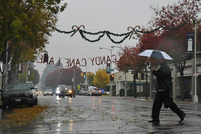 A man crosses rainy Main Street in downtown Visalia on Wednesday, Dec. 4.