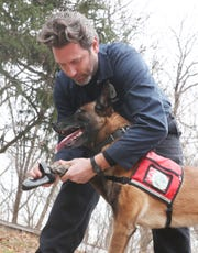 Joshua Beese, Conservation Detection Dog Program Manager, puts little boots on  his dog Fagen while at Croton Point Park Dec. 6, 2019.