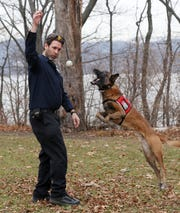 Joshua Beese, Conservation Detection Dog Program Manager, rewards his dog Fagen with a ball after the dog demonstrated how he sniffs out invasive plants and insects that threaten crops, while at Croton Point Park Dec. 6, 2019.