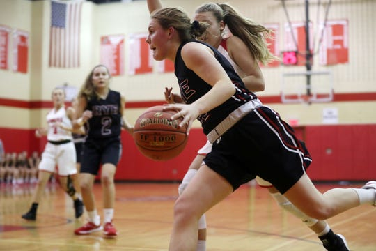 Rye's Teaghan Flaherty (12) drives to the basket in front of Somers' Amy Lasher (1)  during girls basketball action at Somers High School Dec. 5, 2019. Rye won the game 54-35.
