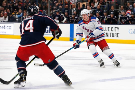 Dec 5, 2019; Columbus, OH, USA; New York Rangers defenseman Adam Fox (23) skates with the puck as Columbus Blue Jackets right wing Gustav Nyquist (14) defends during the second period at Nationwide Arena. Mandatory Credit: Russell LaBounty-USA TODAY Sports