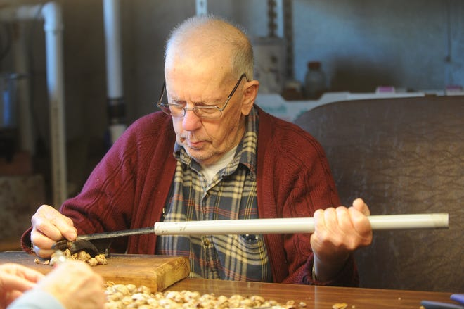 Pete Costello cracks hickory nuts in the basement of his Eden home in this 2014 file photo.