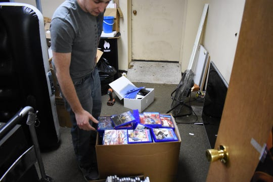Store owner Brandon Parsons sifts through the empty boxes of hundreds of games that were stolen from Bargain Box on Wednesday.