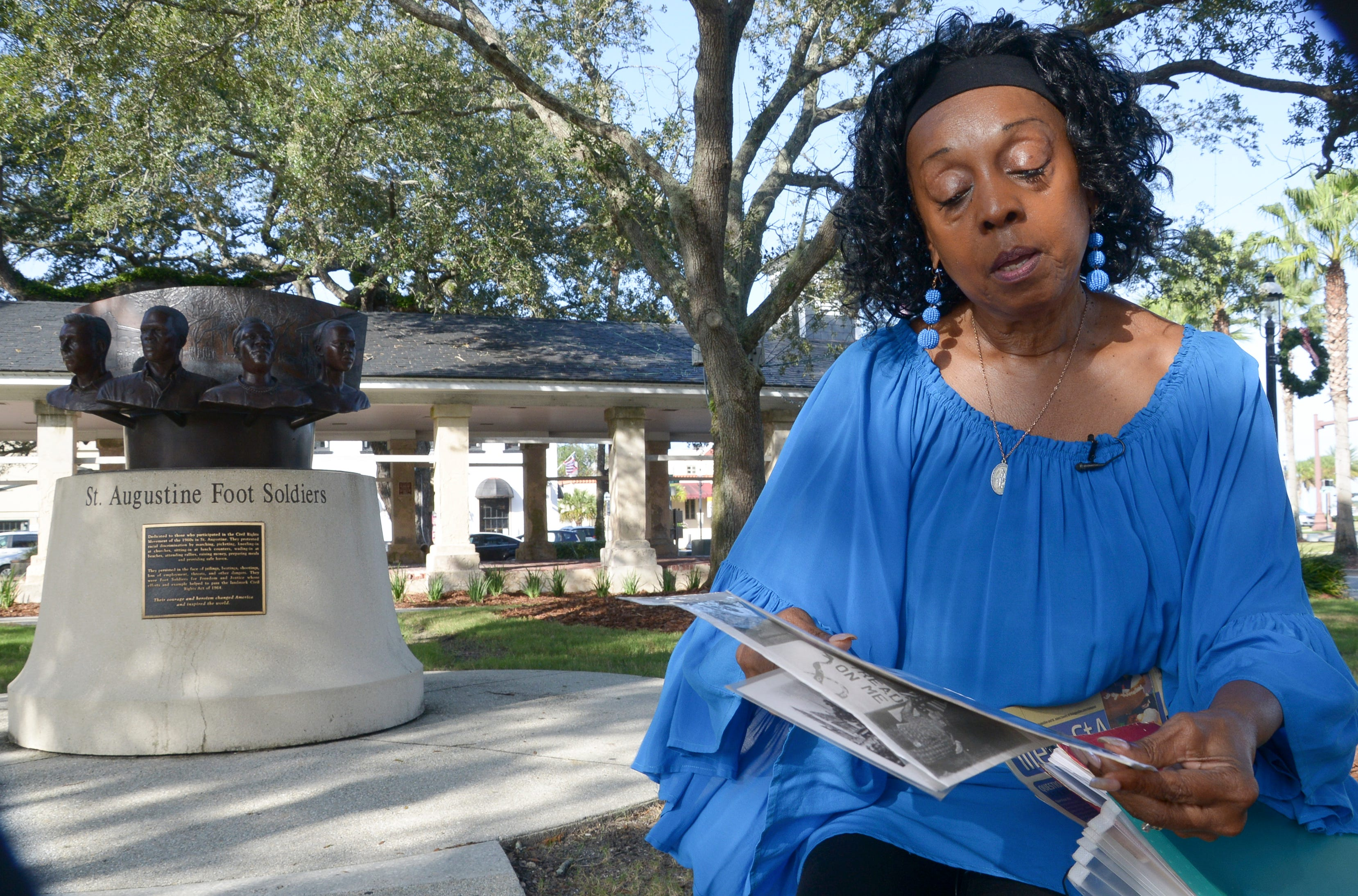 Bernadette Reeves holds photos during the civil rights era marches in St. Augustine as she talks about life in the city. Behind her is the St. Augustine Foot Soldiers, a monument to the people who marched during that period in the 1960s. Behind that is an open pavilion known as The Slave Market.