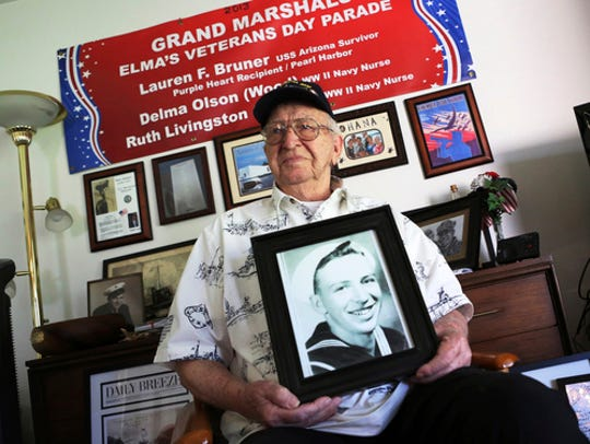 In this Nov. 17, 2016, file photo, Lauren Bruner, a survivor of the USS Arizona that was attacked on Dec. 7, 1941, holds with a 1940 photo of himself at his home in La Mirada, Calif. Divers will place the ashes of Bruner in the wreckage of his ship during a ceremony this weekend in Pearl Harbor, Hawaii.   Bruner died earlier in 2019 at the age of 98.