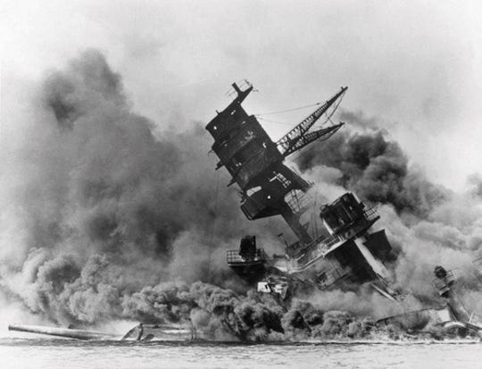 In this Dec. 7, 1941, photo, smoke rises from the battleship USS Arizona as it sinks during the Japanese attack on Pearl Harbor, Hawaii. Divers will place the ashes of Lauren Bruner, a survivor from the USS Arizona in Pearl Harbor, in the wreckage of his ship during a ceremony this weekend.  Bruner died earlier in 2019 at the age of 98.