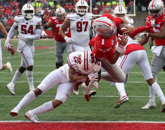 Ohio State quarterback Justin Fields dives past Wisconsin safety Eric Burrell (25) for a touchdown during the third quarter of their game in 2019 at Ohio Stadium.