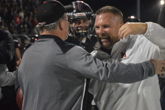 Many coach Jess Curtis (right) hugs one of his assistants after his team won 17-14 over Kentwood Friday. The Tigers are heading to the Class 2A finals for the first time since 2014.