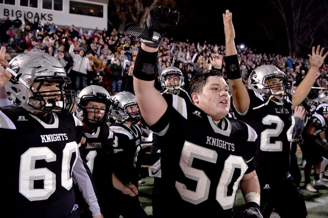 Robbinsville's Jobi Garland, Candler Edwards, and Xavier Rattler celebrate as the final seconds tick down as the Black Knights defeat Thomas Jefferson 28-14 in the 1A West Region final in Robbinsville on Dec. 6, 2019. The Black Knights advanced to the state final game.