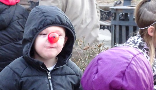 Beau Massey, 5, sports a glowing red nose as his family waits for the Bucyrus Kiwanis-Rotary Santa Parade to begin in downtown Bucyrus on Friday evening.