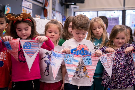Kindergartners hold up their banner to welcome veterans at Harrison Elementary School.