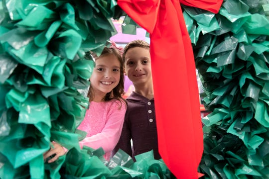 Second grade twins Aliya and Easton Duckworth, 8, pose with one of the wreaths.