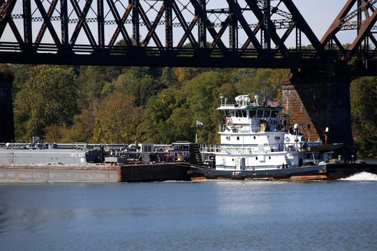 A tugboat moving barges navigates the Ohio River near Monaca, Pa.