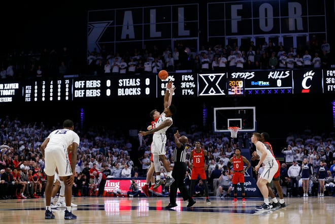 Cincinnati Bearcats center Chris Vogt and Xavier Musketeers forward Tyrique Jones leap for the tip-off in 2019.