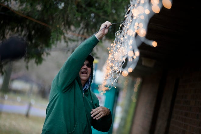 """Jerry Blattner, a member of the """"Grandpa Gang"""" volunteer group, runs a speaker cable on a roof  while preparing for the Light Up Middletown Christmas light display on Friday, Nov. 22, 2019, in Middletown."""