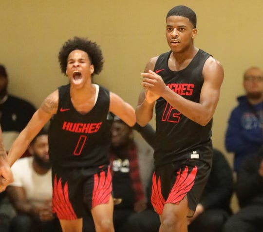 Hughes players Camron McKenzie and  Elijah Madden-Saxon react during Hughes, 63-60 win over Woodward, Friday,  Dec. 6, 2019.