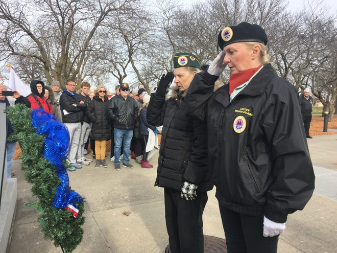 """Members of Amvets Post II, a veterans organization in Des Moines, participate in the laying of the wreath during the Pearl Harbor remembrance ceremony at the Iowa Capitol Saturday afternoon. Katheleen Waters (right) said she feels a special connection to these events as a veteran, saying, """"Once a soldier, always a soldier."""""""