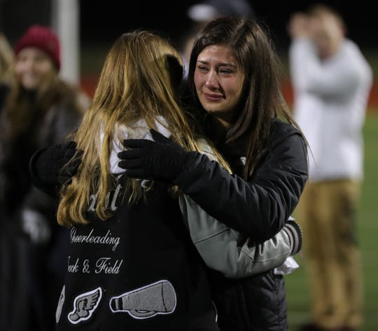 Riley Welton and Emelia Pesci embrace after the memorial held to honor Trevon Tyler on Friday, Dec. 6, 2019 at South Lyon East High School in South Lyon, Mich.