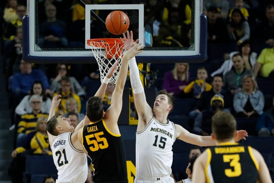 Iowa center Luka Garza shoots against Michigan's Jon Teske, right, and Franz Wagner in the first half in Ann Arbor, Friday, Dec. 6, 2019.