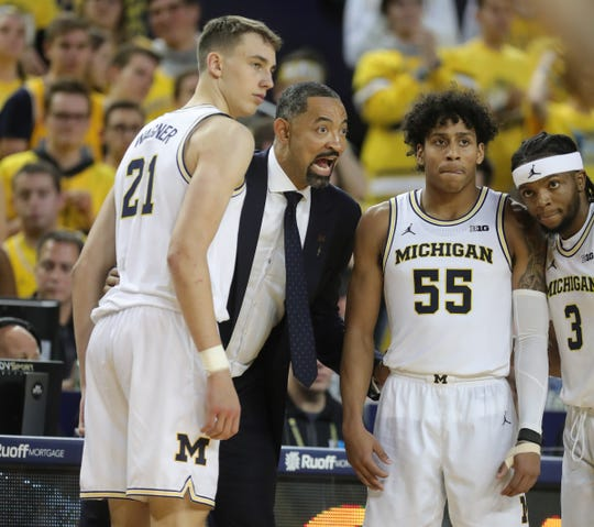 Juwan Howard talks with Michigan guards Franz Wagner (21), Eli Brooks (55) and Zavier Simpson (3) during action against Iowa, Friday, Dec. 6, 2019 at the Crisler Center in Ann Arbor.