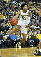 Michigan guard Eli Brooks (55) makes an airborne pass in the first half.
