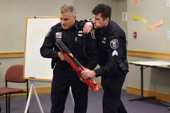 Farmington police Officer Mark Mostek, left, has a toy weapon taken away from him by Sgt. Michael Flatt, during an ALICE training program at the Maxfield Education Center in Farmington.