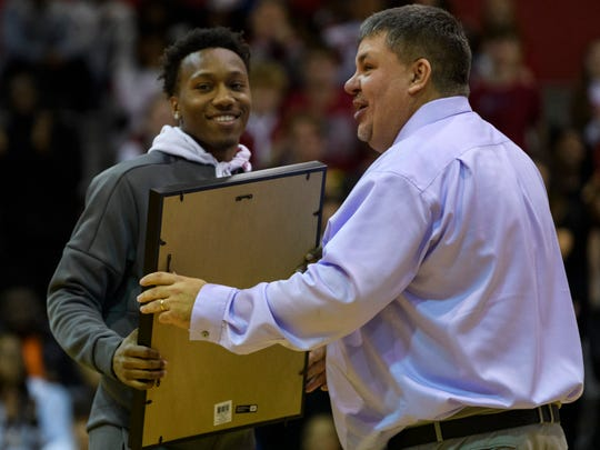 Former Bosse player Mekhi Lairy smiles as Bosse Coach Shane Burkhart hands him a framed jersey during a jersey retirement ceremony at the season opening game against the Terre Haute South Braves in Evansville, Friday evening, Dec. 6, 2019. Lairy broke the city's all-time scoring record in 2018 and currently plays for the Miami (Ohio) Redhawks.