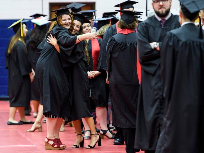University of Southern Indiana graduates Cheyenne Welte, left, and Ashley Bittner, right, embrace as they take a selfie together before the start of the Romain College of Business and College of Liberal Arts ceremony held inside USI's Screaming Eagles Arena in Evansville, Ind., Saturday, Dec. 7, 2019. More than 690 students from 21 states and 10 countries received degrees from USI during the two ceremonies held on Saturday.