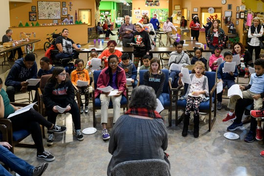 People of all ages gather to sing Christmas carols with volunteer Nancy Roberts, front center, during the Christmas Extravaganza party at Patchwork Central in Evansville, Thursday evening, Dec. 5, 2019.
