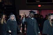 Osei Debrah gives a thumbs-up as he walks to receive his degree at the University of Southern Indiana commencement in Evansville, Saturday, Dec. 7, 2019.