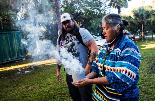 Betty Osceola, right, a member of the Miccosukee Tribe and Garrett Stuart, who was Lakota raised prepare for tribal ceremony before a prayer walk on Loop Road off of the Tamiami Trail on Saturday Dec. 7. 2019. The walk was held to raise awareness for private land owners who feel threatened by the Western Everglade Restoration Project. The Miccosukee Tribe is directly within the restoration project.
