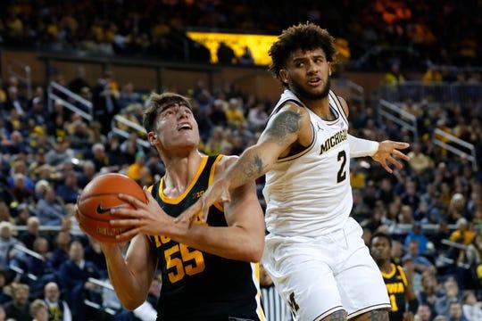 Michigan forward Isaiah Livers (2) fouls Iowa center Luka Garza (55) in the second half of an NCAA college basketball game in Ann Arbor, Mich., Friday, Dec. 6, 2019. (AP Photo/Paul Sancya)