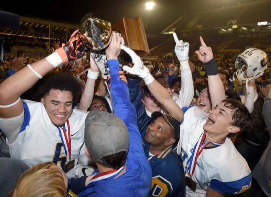 The Oxford Chargers celebrate with the Class 6A trophy at the MHSAA State Football Championships at M.M. Roberts Stadium on the University of Southern Mississippi campus in Hattiesburg on Friday, December 6, 2019.