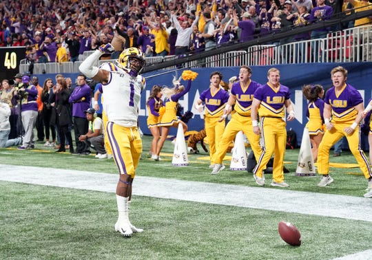 Dec 7, 2019; Atlanta, GA, USA; LSU Tigers wide receiver Ja'Marr Chase (1) celebrates his touchdown against the Georgia Bulldogs during the first quarter of the the 2019 SEC Championship Game at Mercedes-Benz Stadium. Mandatory Credit: John David Mercer-USA TODAY Sports