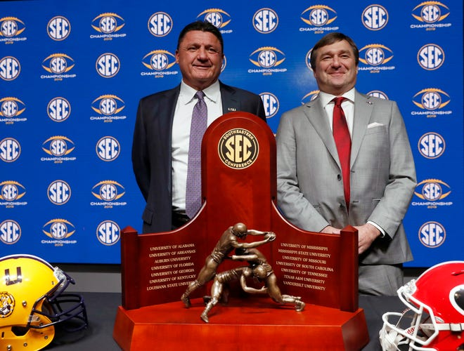LSU head coach Ed Orgeron, left, and Georgia head coach Kirby Smart pose for a photo with the trophy during news conference ahead of Saturday's NCAA college SEC Championship football game Friday, Dec. 6, 2019, in Atlanta. (AP Photo/John Bazemore)