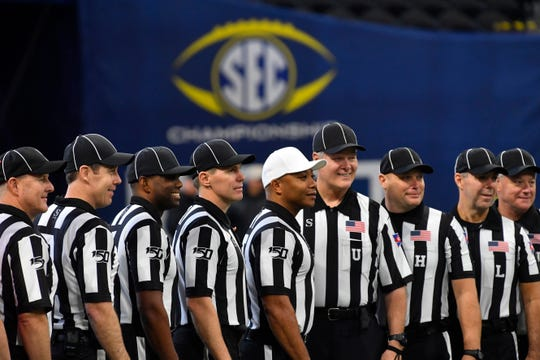 Officals pose for a photo ahead of the first half of the Southeastern Conference championship NCAA college football game between LSU and Georgia, Saturday, Dec. 7, 2019, in Atlanta. (AP Photo/John Amis)