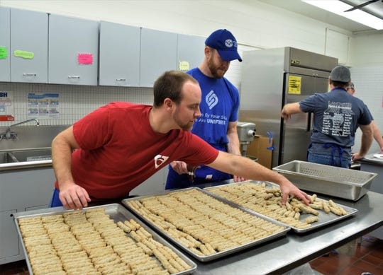 Matt Poston reaches for more sausages as he and Rusty Azbell, prepare the next wave to be cooked Lancaster Kiwanis Club Pancake Festival Dec. 7. They estimated they cook around 6,000 sausages for the festival, which is the club's biggest fundraiser of the year.