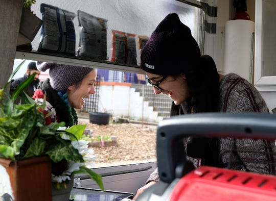 Christabelle Dozeman, right, jokes with a customer Saturday, Dec. 7, 2019 from her VEG-N food truck outside The Fledge in Lansing.