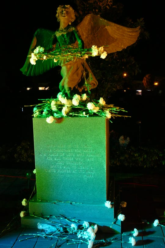 Inspired in the book The Christmas Box by Richard Paul Evans, Marco Island's Christmas Box Angel was inaugurated in 2000 to provide a place for parents and grandparents to remember their children and grandchildren who have passed away. In the picture, attendants of the memorial service left flowers by the angel statue at the local cemetery on Dec. 6, 2019.