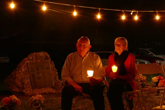 A man and a woman hold lighted candles during the 20th Marco Island Christmas Box Angel Memorial Service at the local cemetery on Dec. 6.