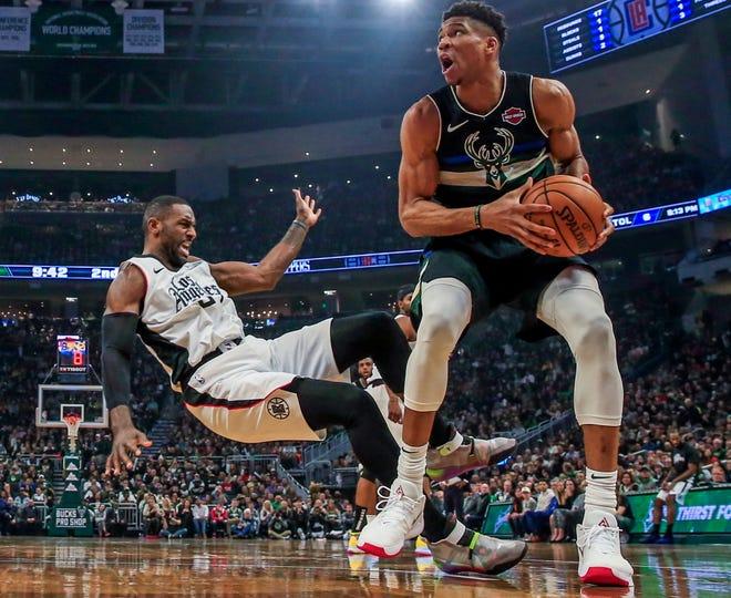 Milwaukee Bucks forward Giannis Antetokounmpo prepares to shoot as Los Angeles Clippers forward Patrick Patterson falls to the floor.